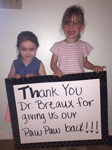 Larry Edmonson's grandkids, Aubrey Burge and Taylor Evans, thanking Dr. Breaux for saving his life with a sign that says 'Thank you Dr. Breaux for giving us our Paw Paw back!'